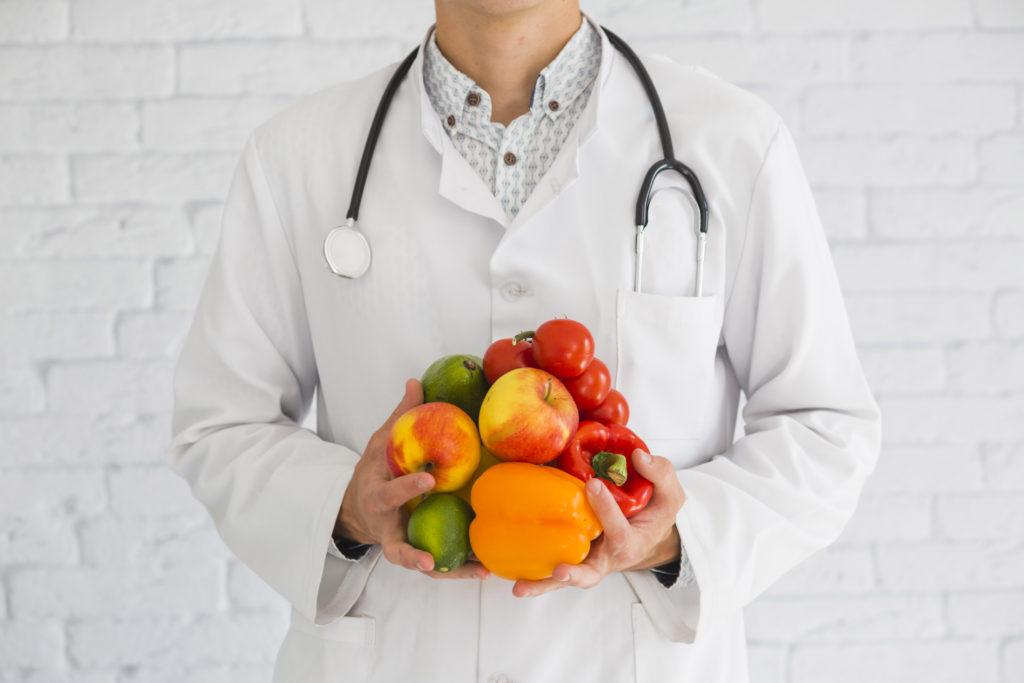 medico con della frutta e della verdura in mano